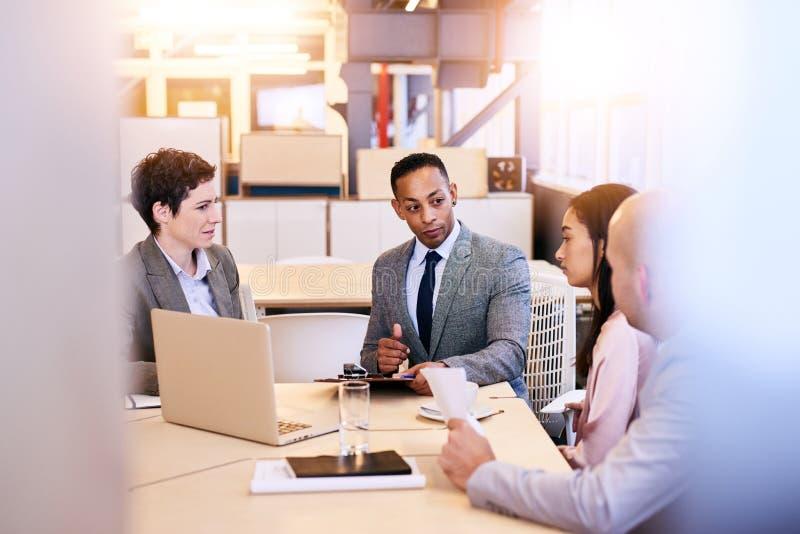 Un gruppo eclettico di quattro professionisti di affari che conducono una riunione immagine stock libera da diritti