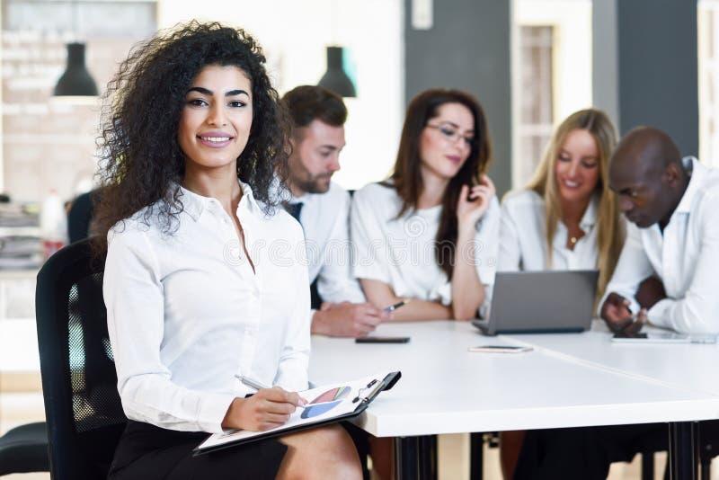 un gruppo Multi-etnico di tre persone di affari che si incontrano in una o moderna immagine stock