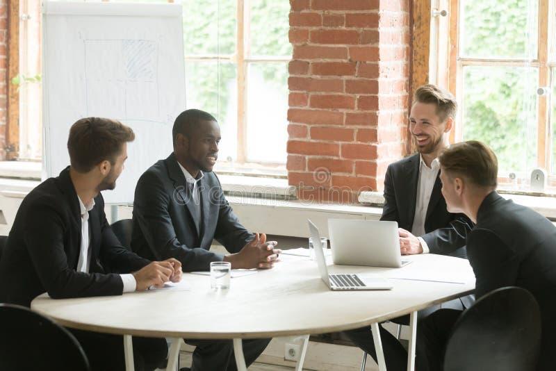 Un gruppo sorridente soddisfatto di quattro uomini d'affari che parla ridendo del mee immagine stock