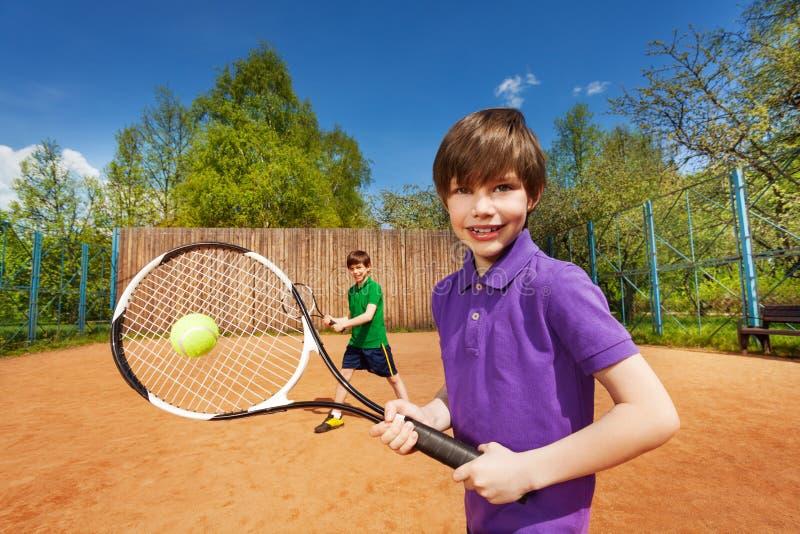 Un gruppo sportivo di due ragazzi che aspettano pallina da tennis fotografia stock libera da diritti