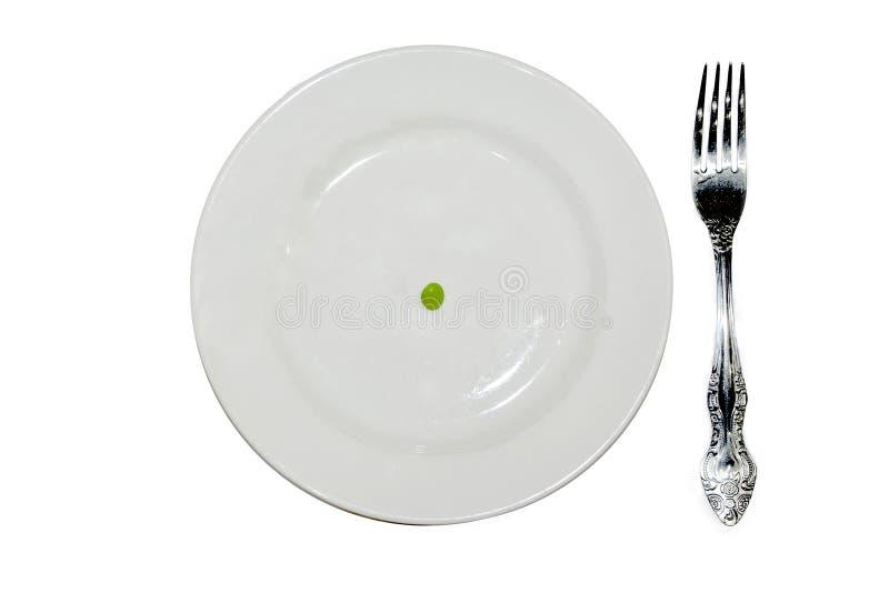 Un guisante en una placa blanca vacía con el cuchillo y la bifurcación foto de archivo