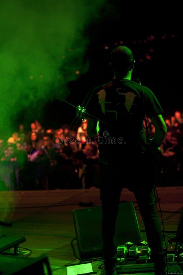Un guitariste avec le microphone sur l'étape photo libre de droits