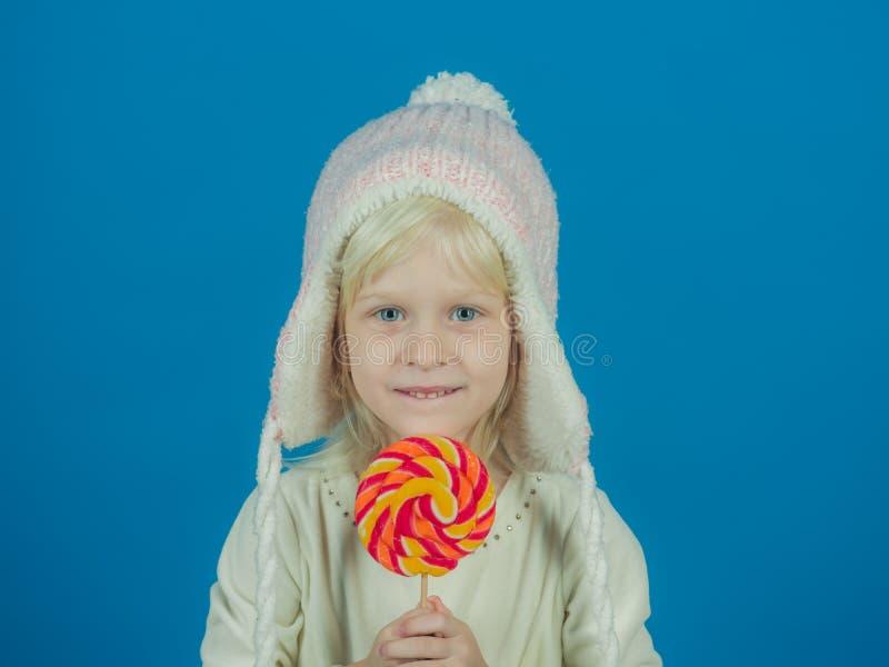 Un gusto por lo dulce Piruleta del control de la niña en el palillo Poco niño con la piruleta dulce Muchacha feliz del caramelo N foto de archivo libre de regalías
