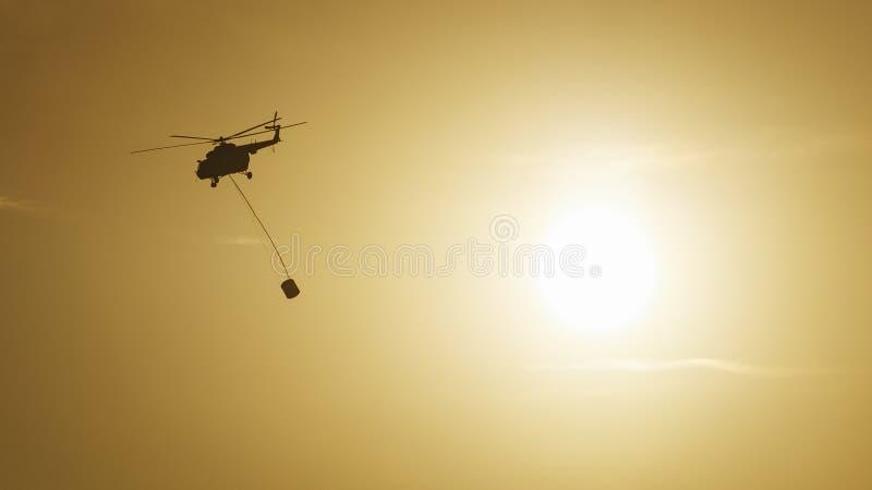 Un hélicoptère de sapeur-pompier se précipite pour aider éteint un feu de forêt photos stock