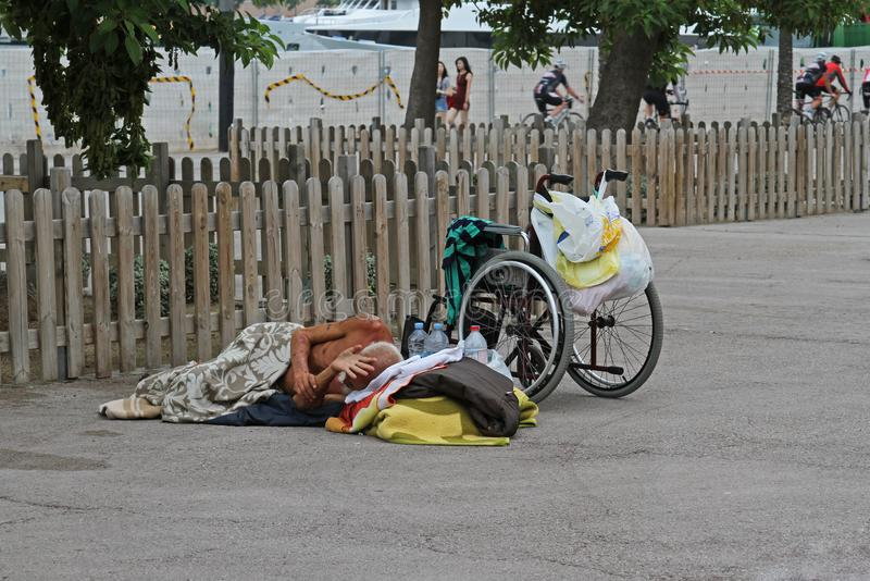 Un handicapé sans abri avec un fauteuil roulant dormant sur l'asphalte à Barcelone images stock