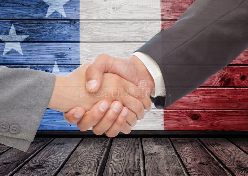 Un handshake di due uomini contro un fondo di legno con la bandiera americana fotografia stock libera da diritti