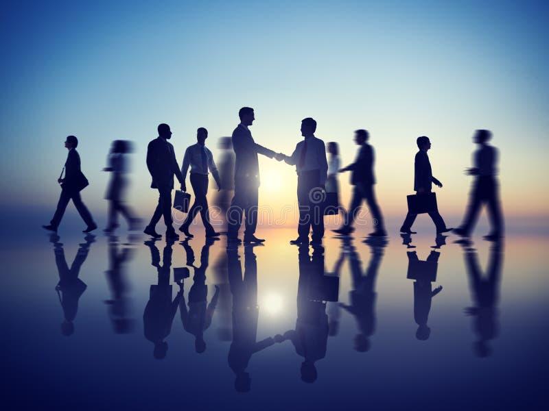 Un handshake di due uomini d'affari insieme ai loro colleghi immagini stock