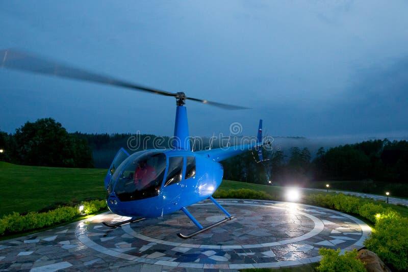 Un helicóptero azul se parquea en un helipuerto privado contra una tarde azul fotografía de archivo