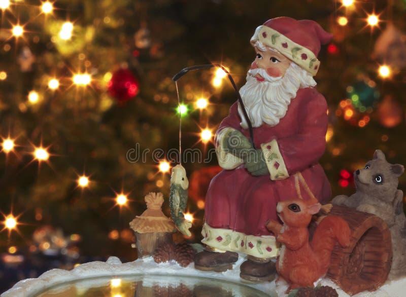 Un hielo que pesca Papá Noel y a amigos peludos imagen de archivo