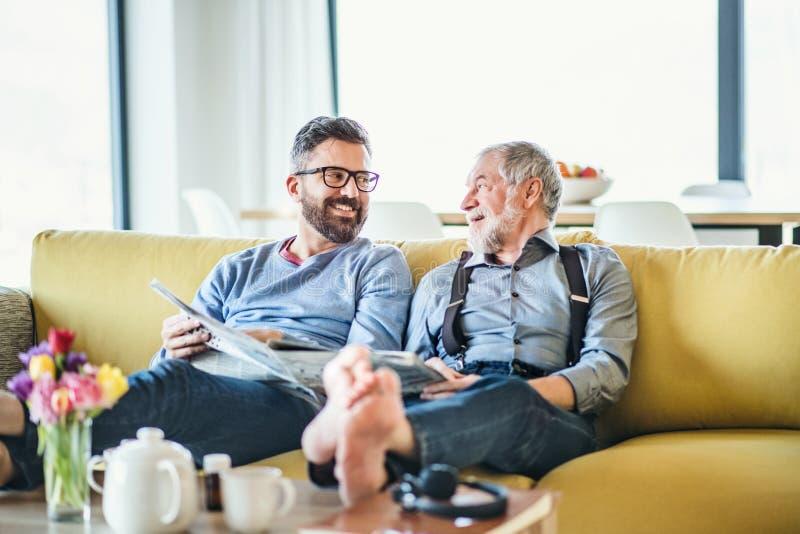 Un hijo adulto del inconformista y un padre mayor que se sientan en el sofá dentro en casa, hablando imagenes de archivo