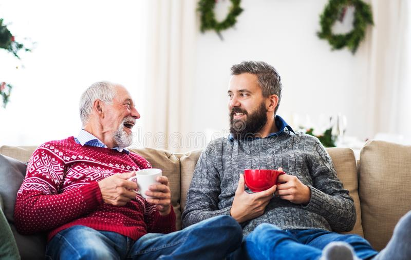 Un hijo mayor del padre y del adulto que se sienta en un sofá en casa en el tiempo de la Navidad, hablando foto de archivo
