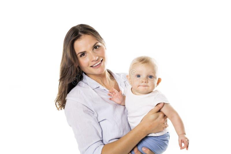 Un holdng de mère son bébé sur le fond de blanc de studio image stock