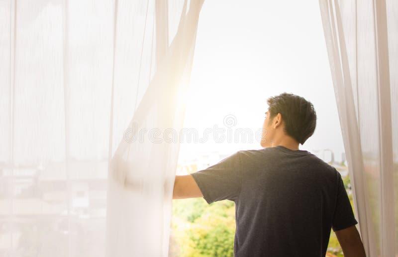 Un hombre abre la ventana para ver afuera foto de archivo libre de regalías