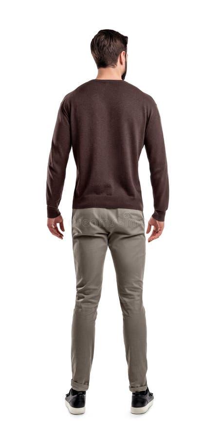 Un hombre adulto en soportes casuales del suéter en una visión trasera con los brazos relajados y su cabeza dobló levemente de la fotos de archivo