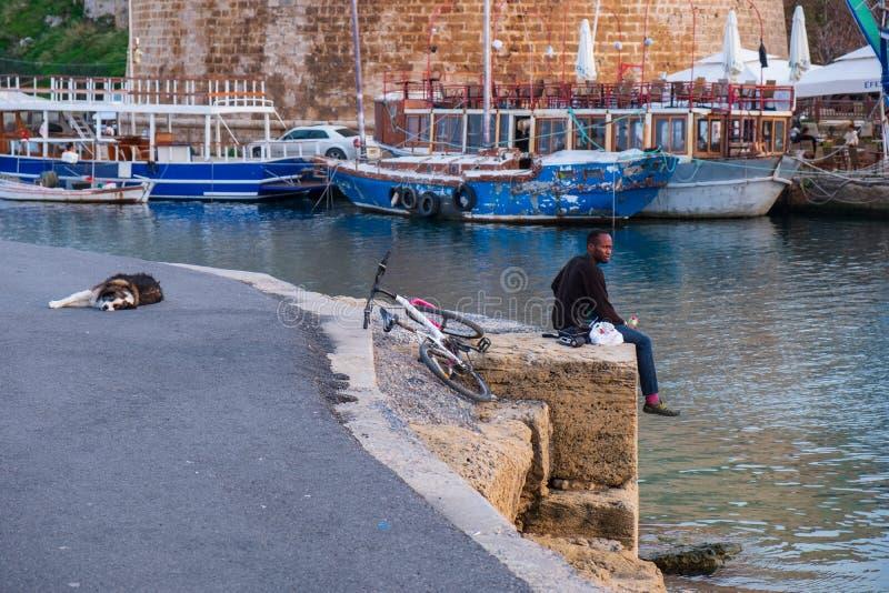 Un hombre africano se sienta por el mar en el puerto viejo de Kyrenia en Chipre mientras que un perro cerca de él está durmiendo  fotografía de archivo libre de regalías