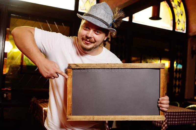 Un hombre alegre gordo en un sombrero bávaro con una pluma durante la celebración de Oktoberfest sostiene una muestra o una pizar fotografía de archivo libre de regalías