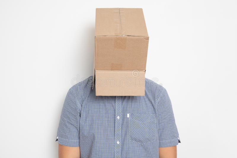 Un hombre anónimo con una caja en su cabeza que encubre su identidad I imagenes de archivo