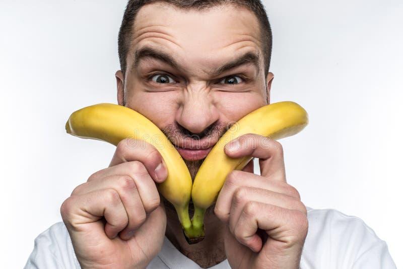 Un hombre anormal en la camisa blanca está sosteniendo dos plátanos cerca de su cara y está haciendo caras divertidas Este vegano imágenes de archivo libres de regalías