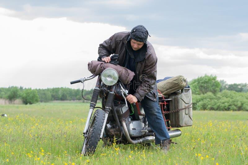 Un hombre apocalíptico de los posts en la motocicleta en un prado foto de archivo libre de regalías