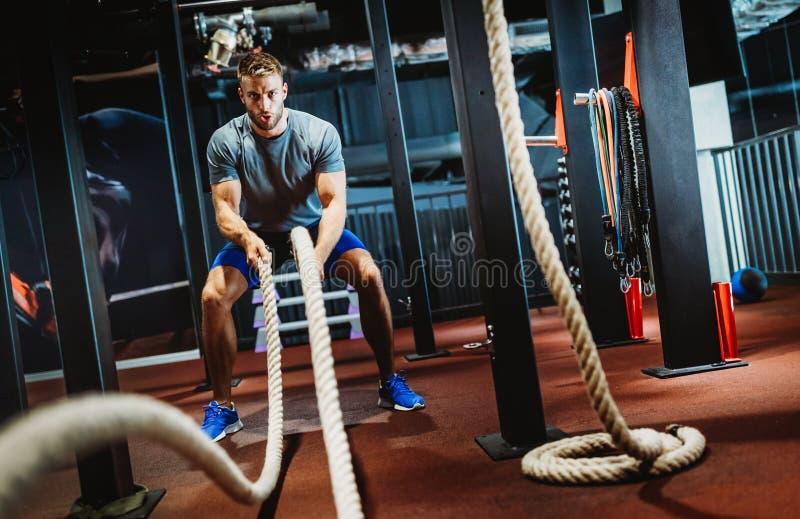 Un hombre apropiado trabajando con cuerdas de batalla en el gimnasio foto de archivo