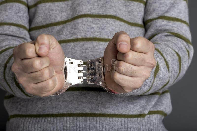 Un hombre arrestado con las esposas imagen de archivo