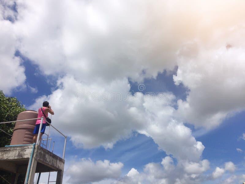 Un hombre ascendente hasta la fotografía el cielo de la mañana con una nube blanca mullida fotografía de archivo