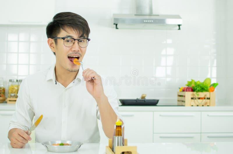 Un hombre asi?tico est? desayunando en la ma?ana foto de archivo