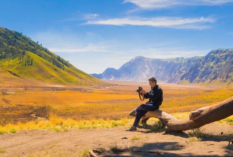 Un hombre asiático, un fotógrafo, sosteniendo una cámara en la colina de verde de la sabana de Bromo en viaje del viaje y concept imagenes de archivo