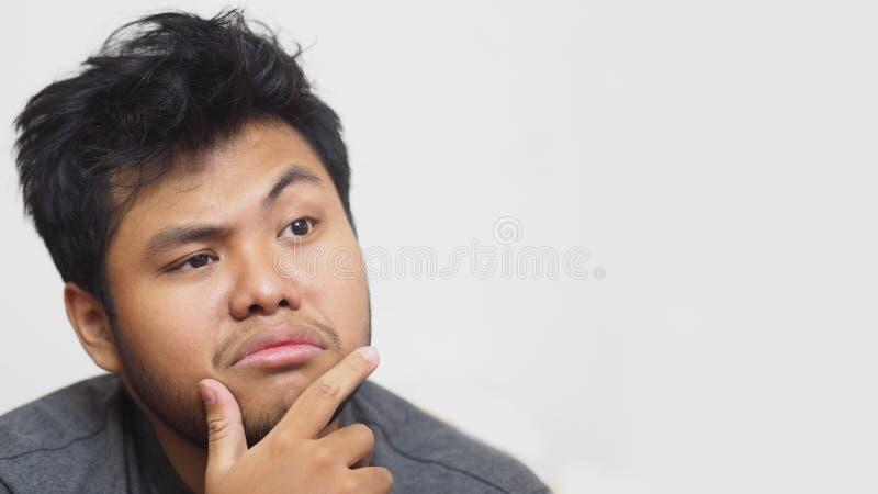 Un hombre asiático joven confuso en el fondo blanco imagenes de archivo