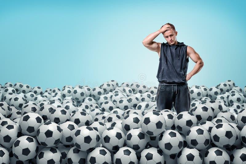 Un hombre atlético preocupado se coloca dentro de un montón enorme de las bolas idénticas del fútbol imagenes de archivo