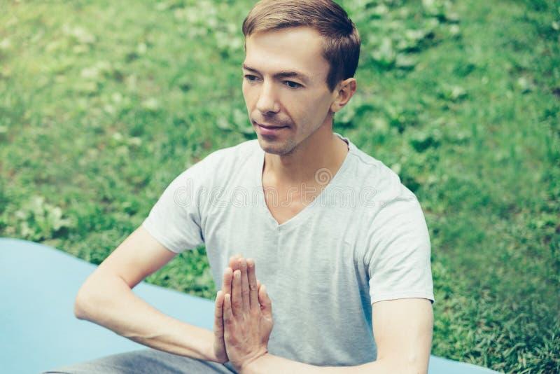 Un hombre atractivo joven practica yoga en naturaleza y medita en la posición de loto respecto a un césped verde visi?n desde arr fotos de archivo