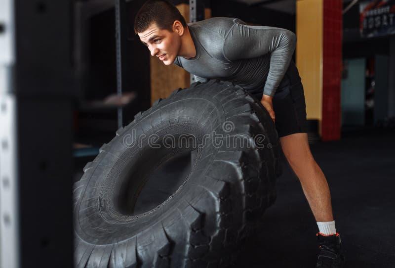 Un hombre aumenta un grande rueda adentro el gimnasio, entrenando para la masa del músculo foto de archivo libre de regalías