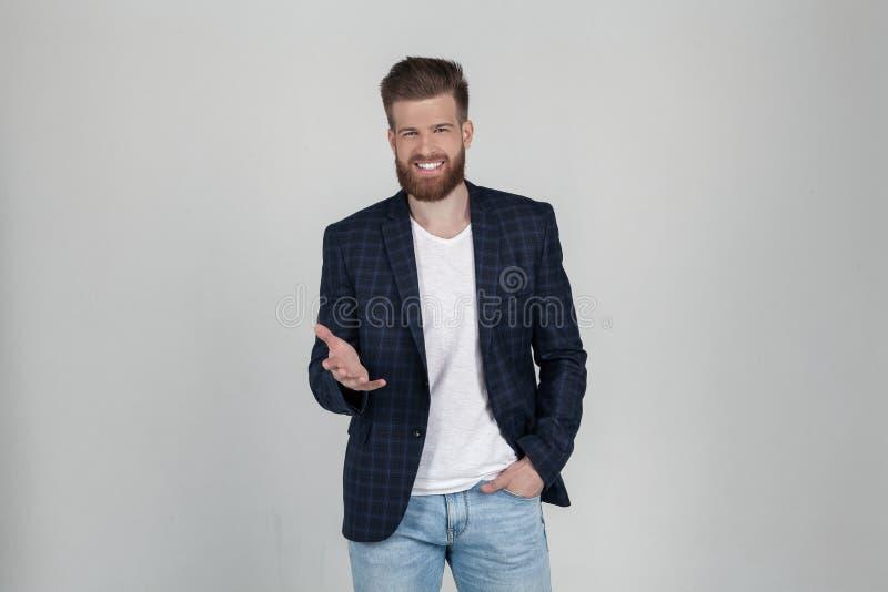Un hombre barbudo atractivo hermoso en una chaqueta tiene expresión positiva, puntos con el dedo índice a la cámara ?l se coloca  fotografía de archivo