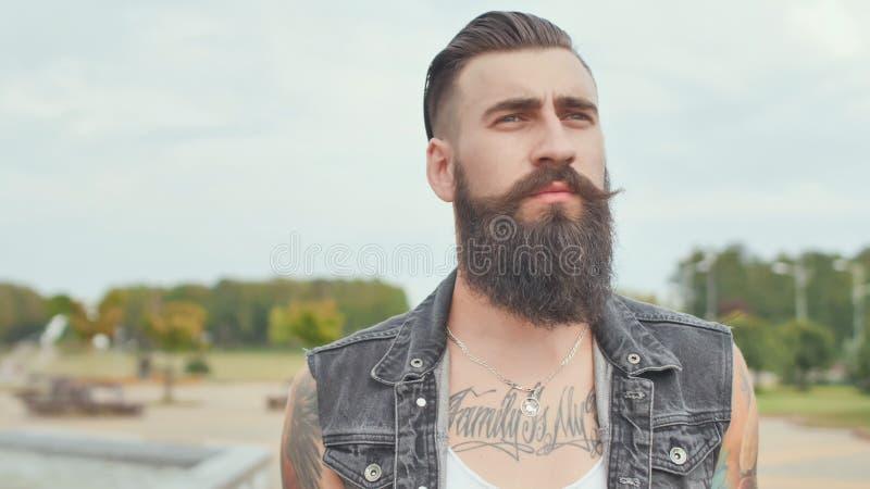 Un hombre barbudo brutal con los tatuajes camina a través de la ciudad con un bolso negro imagenes de archivo