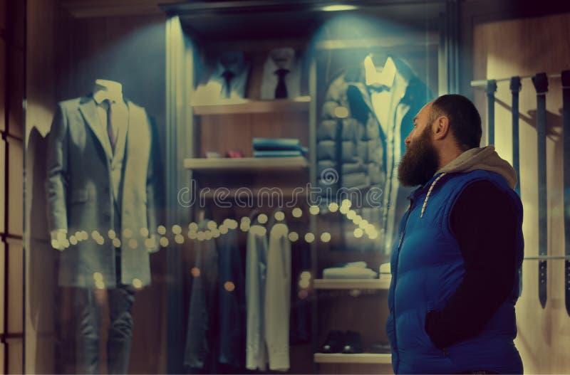 Un hombre barbudo en miradas del sporstwear a la ventana de la tienda con ropa del negocio foto de archivo libre de regalías