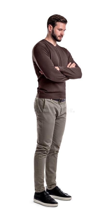 Un hombre barbudo en ropa casual elegante se coloca en media vuelta con los brazos doblados y mira abajo foto de archivo