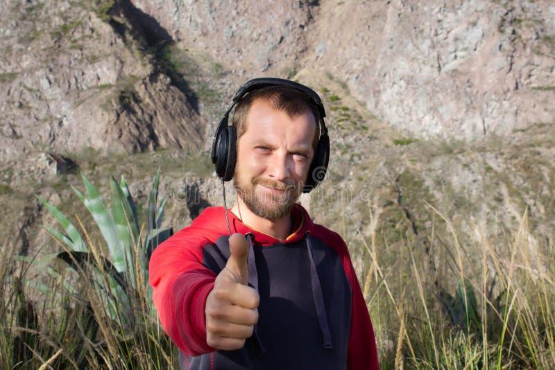 Un hombre barbudo escucha la música en los auriculares, en naturaleza Hay montañas detrás de él Él muestra su pulgar para arriba foto de archivo