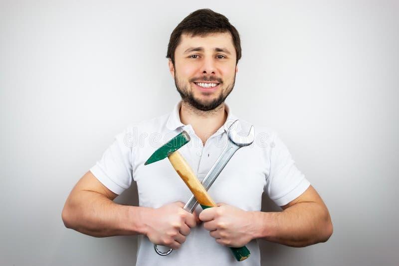 Un hombre barbudo feliz sonriente en una camiseta blanca con un martillo y una llave, sosteniéndolos de través foto de archivo
