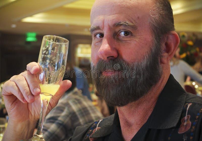 Un hombre barbudo goza de una mimosa en un restaurante fotografía de archivo libre de regalías