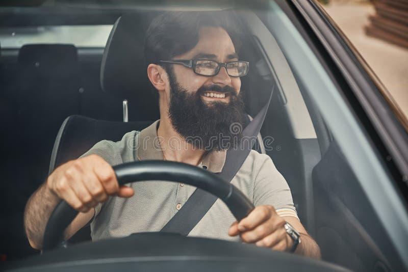 Un hombre barbudo moderno que conduce un coche imagen de archivo