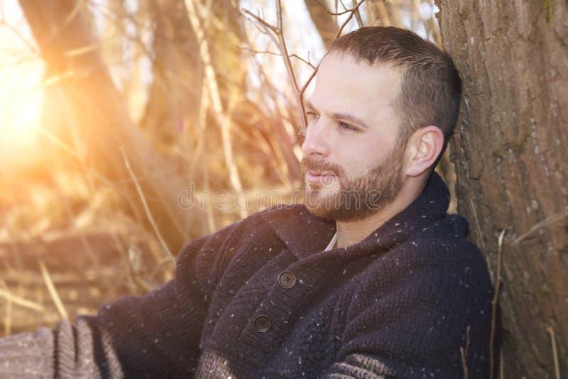 Un hombre barbudo pensativo en la puesta del sol del bosque fotografía de archivo