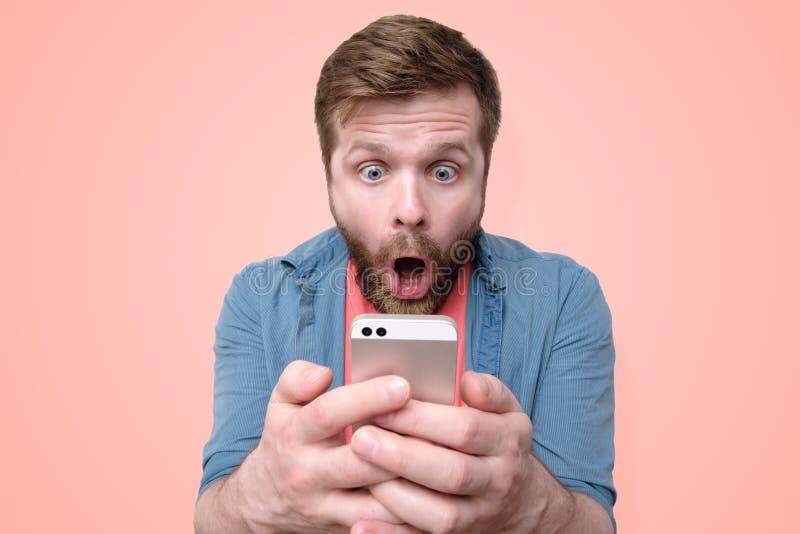 Un hombre barbudo sorprendido, chocado sostiene un smartphone en sus manos y miradas en la exhibición con su boca abierta y los o fotografía de archivo