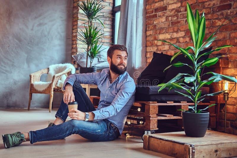 Un hombre bebe el café en un cuarto con el interior del desván fotografía de archivo