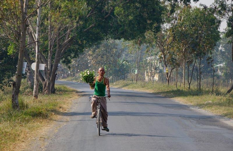 Un hombre biking en el camino rural en Inle, Myanmar fotografía de archivo