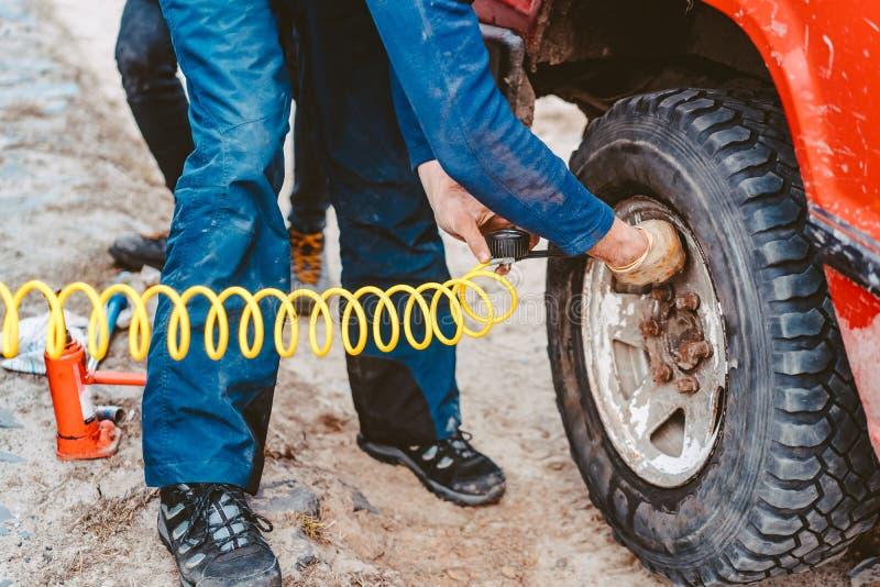 Un hombre bombea la rueda del aire con un compresor imagen de archivo