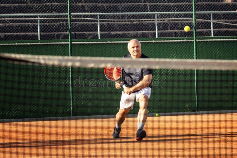 Un hombre calvo de mediana edad juega emocionalmente a tenis en la corte outdoor fotos de archivo libres de regalías