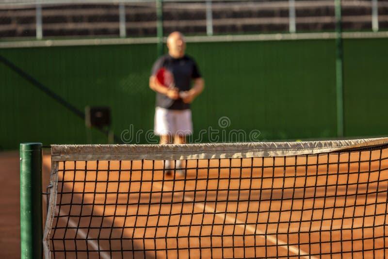 Un hombre calvo de mediana edad juega a tenis en la corte al aire libre D?a asoleado blur imágenes de archivo libres de regalías