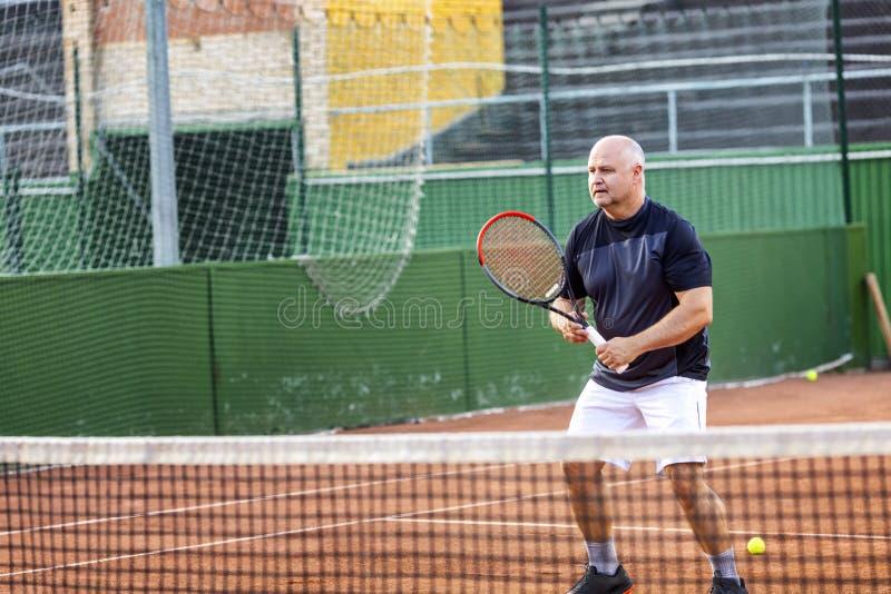 Un hombre calvo de mediana edad juega a tenis en la corte al aire libre D?a asoleado imagen de archivo libre de regalías