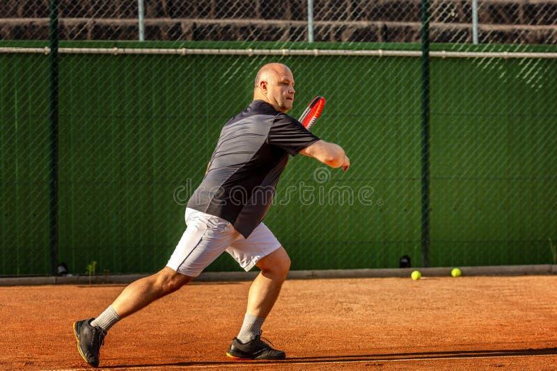 Un hombre calvo de mediana edad juega a tenis en la corte al aire libre D?a asoleado fotos de archivo