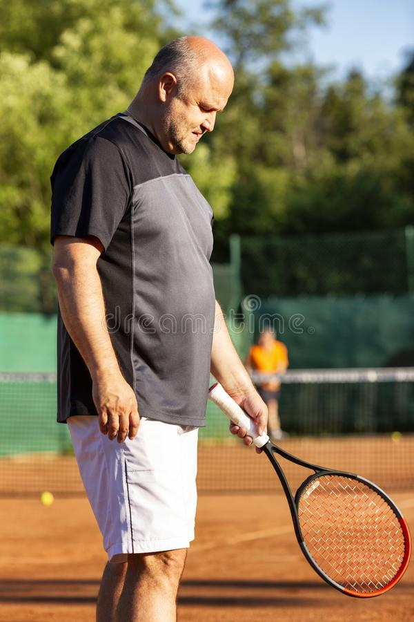 Un hombre calvo de mediana edad juega a tenis en la corte al aire libre D?a asoleado vertical fotos de archivo libres de regalías